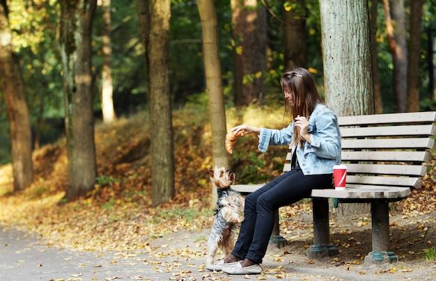 Женщина обедает во время прогулки с собакой Бесплатные Фотографии