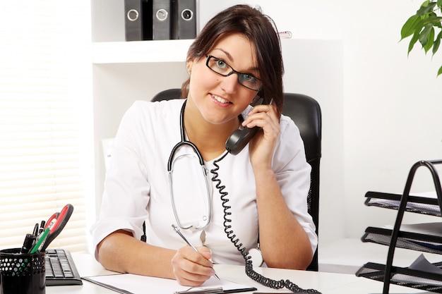電話で話している若い女性医師 無料写真