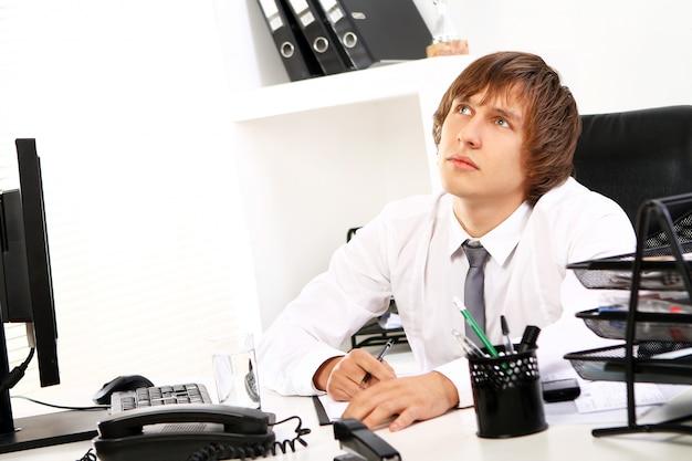 オフィスで考えている青年実業家 無料写真