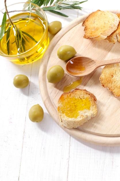 オリーブオイルとパンと木のスプーン 無料写真