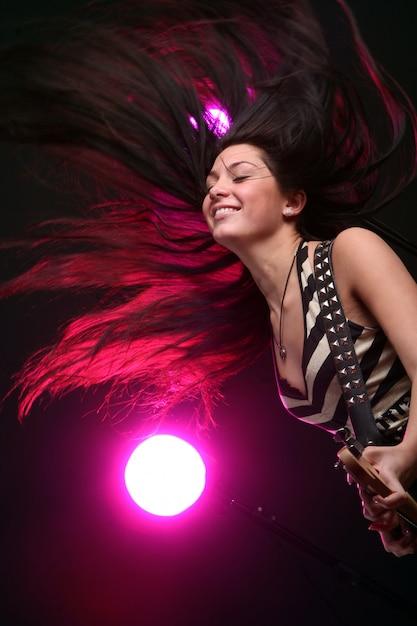 Счастливая улыбающаяся девочка играет на гитаре Бесплатные Фотографии