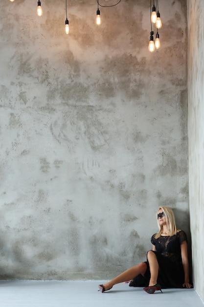 Блондинка с маской в форме летучей мыши для хэллоуина или маскарада и черного костюма Бесплатные Фотографии