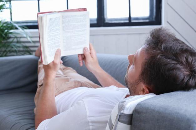 ソファで本を読んでハンサムな男 無料写真