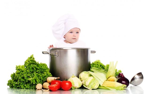 大きな鍋と野菜でかわいい赤ちゃんシェフ 無料写真