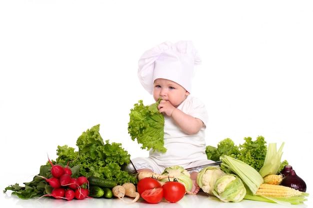 Ребенок с шляпным шеф-поваром в окружении овощей Бесплатные Фотографии