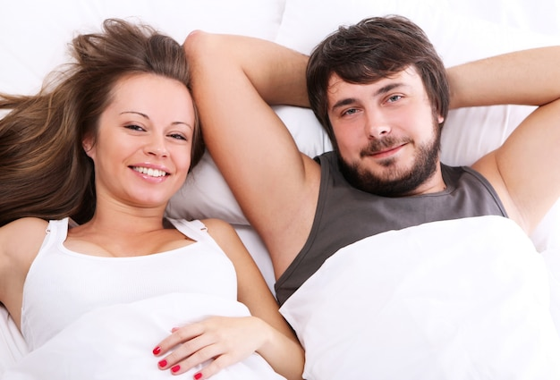 笑顔のカップルがベッドでリラックス 無料写真