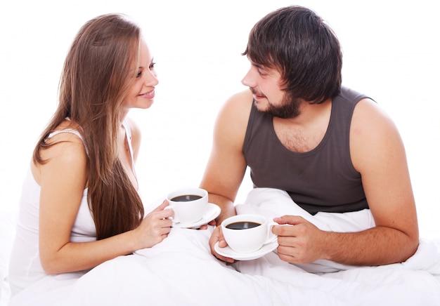 Молодая пара пьет кофе в постели Бесплатные Фотографии