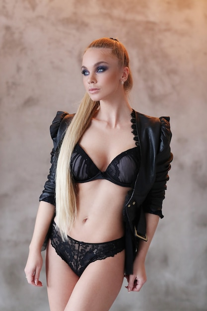黒革のジャケットとセクシーな黒のランジェリーを着ている美しい女性 無料写真