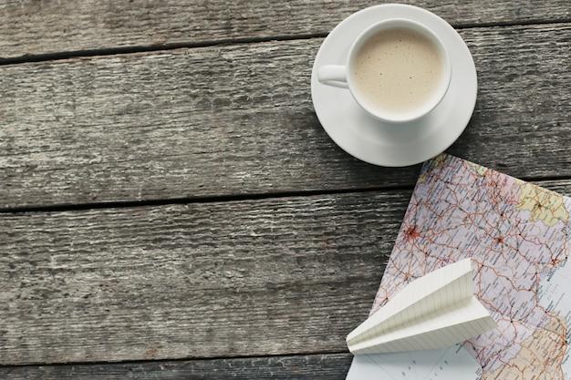 Карта путешествия, бумажный самолетик и кофейная чашка Бесплатные Фотографии