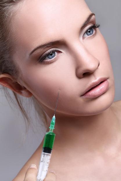 Молодая женщина, впрыскивая для косметических процедур Бесплатные Фотографии