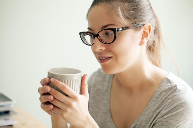 コーヒーを飲みながらメガネの女の子 無料写真