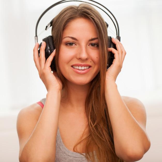 美しい女性は、ヘッドフォンで音楽を楽しむ 無料写真