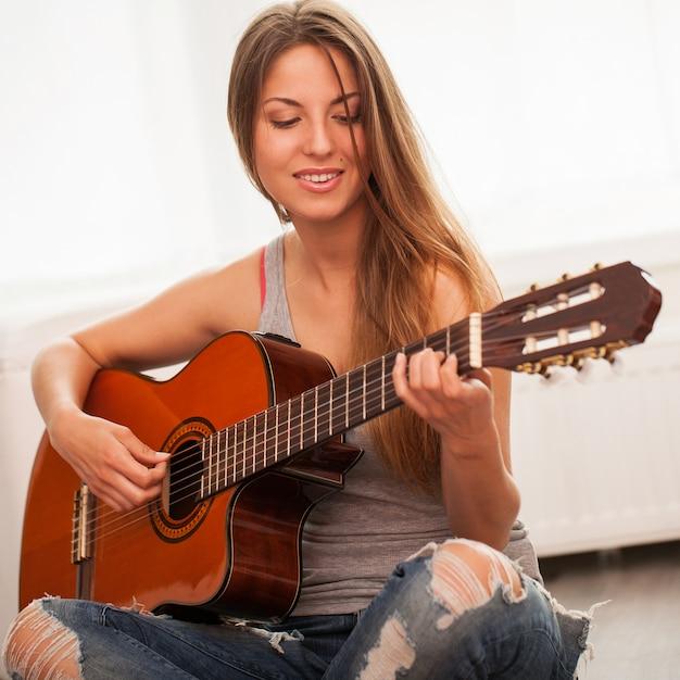 ギターを弾く若い美しい女性 無料写真