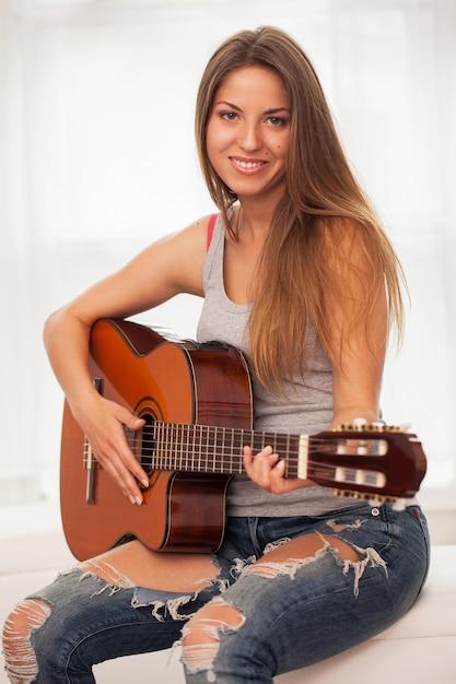 Молодая красивая женщина играет на гитаре Бесплатные Фотографии