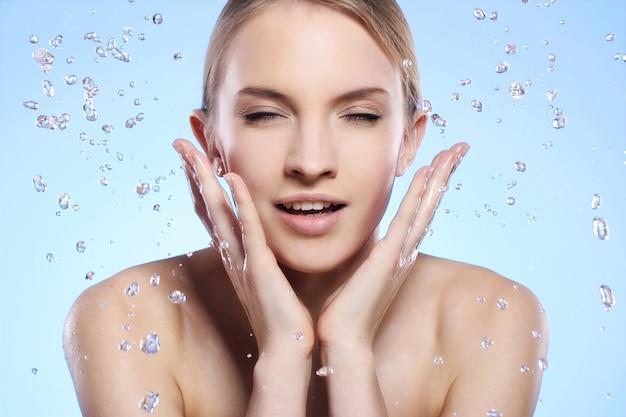 美しい女性が彼女の顔を洗う 無料写真