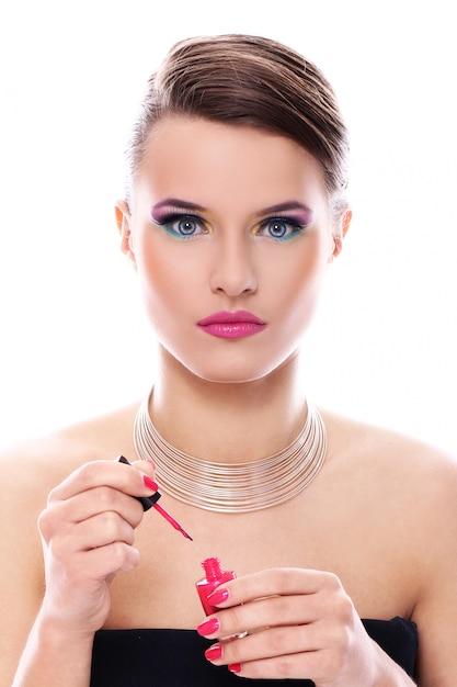 Красивая женщина с бутылкой розового лака для ногтей Бесплатные Фотографии