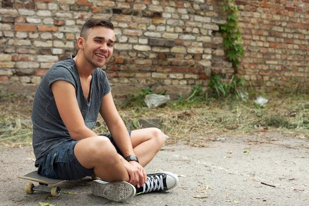 通りに座っているハンサムな男 無料写真