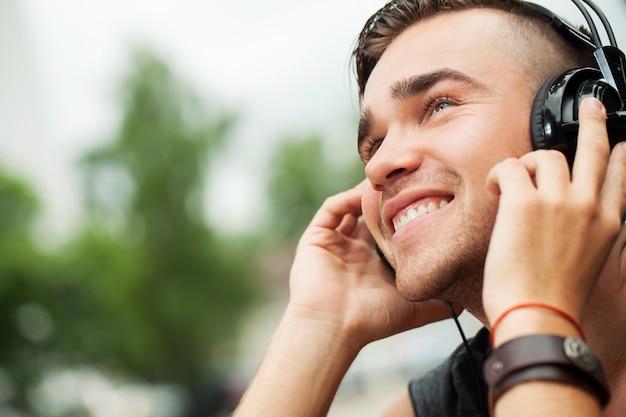 ヘッドフォンで通りに座っているハンサムな男 無料写真