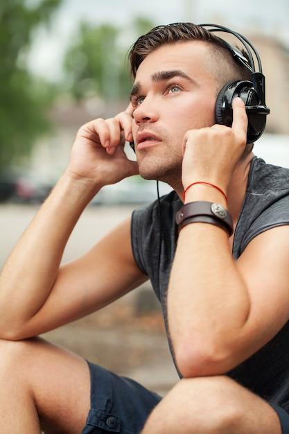 Красивый мужчина сидит на улице с наушниками Бесплатные Фотографии