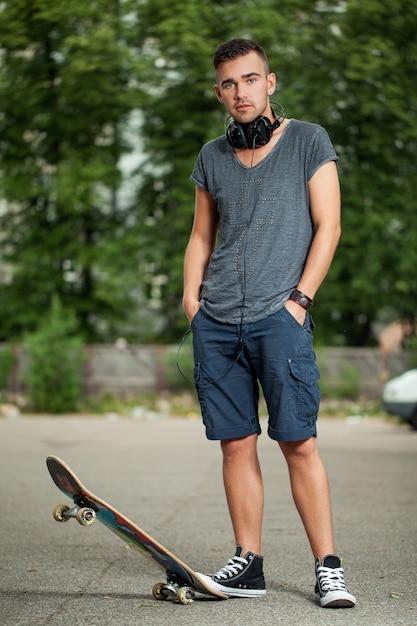 ヘッドフォンとスケートボードのハンサムな男 無料写真