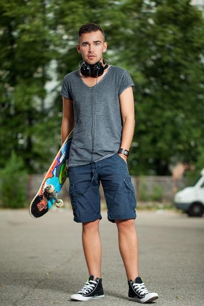 Красивый парень с наушниками и скейтбордом Бесплатные Фотографии
