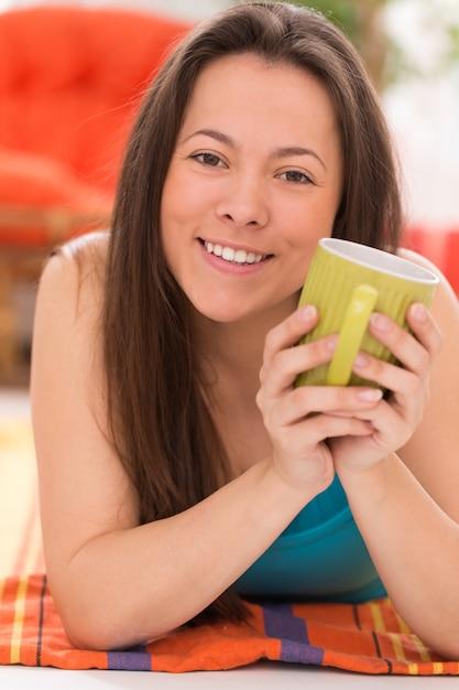 茶マグカップを持つ若い美しい女性 無料写真