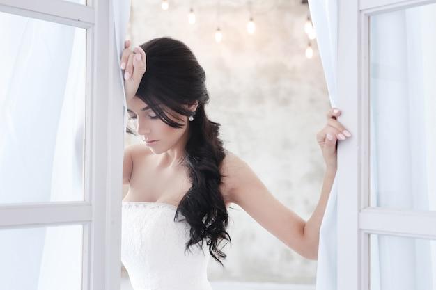 花の花束を保持しているウェディングドレスの美しい花嫁の女性 無料写真