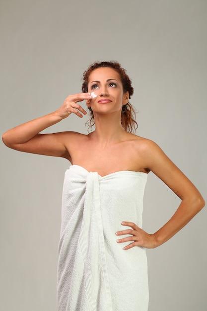 顔にクリームを持つ美しい女性 無料写真