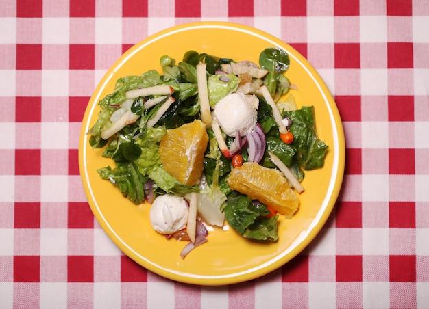テーブルクロスの上の皿に新鮮なおいしいサラダ 無料写真