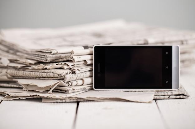 スマートフォンを搭載した新聞の山 無料写真