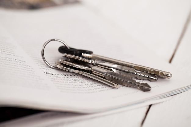 Ключи и журнал на белом столе Бесплатные Фотографии