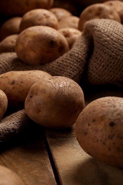 机の上の素朴な皮が付いていないジャガイモ 無料写真