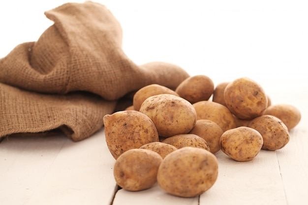 テーブルの上の素朴な皮が付いたままのジャガイモ 無料写真