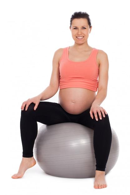 ボールの上に座って妊娠中の女性 無料写真