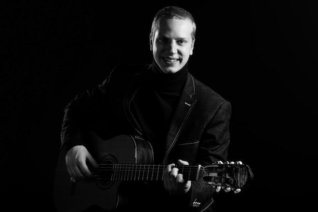 音楽。ギターを抱えて黒のスーツの若い音楽家 無料写真