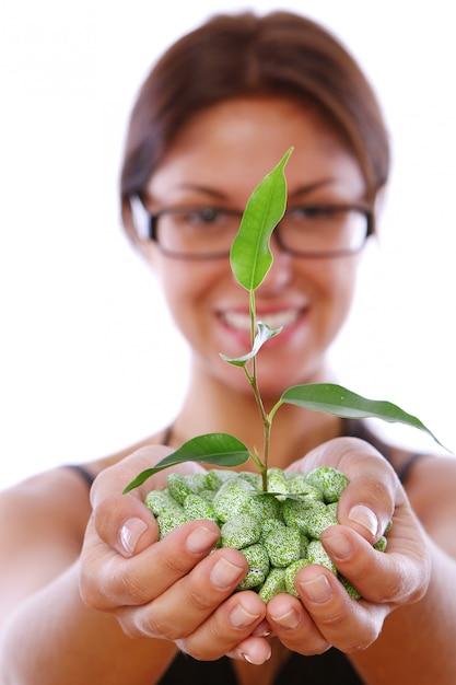 Руки женщины, принимая зеленое растение Бесплатные Фотографии