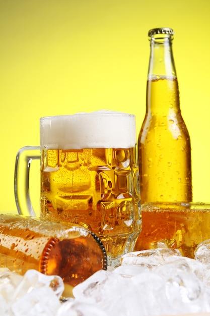 黄色の背景に泡とビールのグラス 無料写真