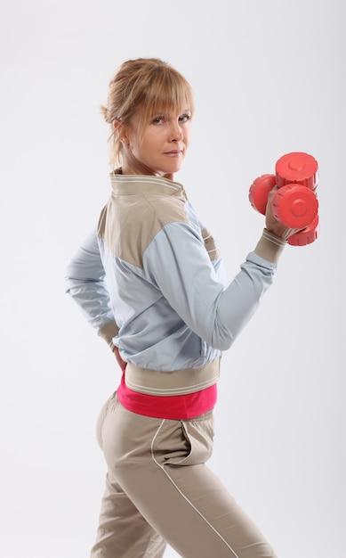 Женщина делает упражнения с видом гантелей со спины Бесплатные Фотографии