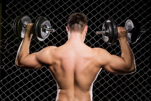 Мощный парень с гантелями показывает мышцы на заборе Бесплатные Фотографии
