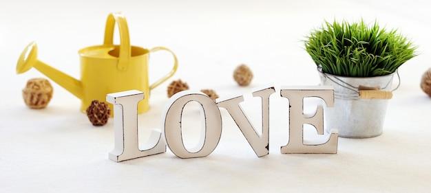 Слово любовь, лейка и трава на столе Бесплатные Фотографии