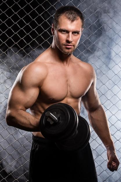 ダンベルフェンスの上の強い男 無料写真