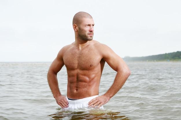 ビーチで魅力的で幸せな男 無料写真