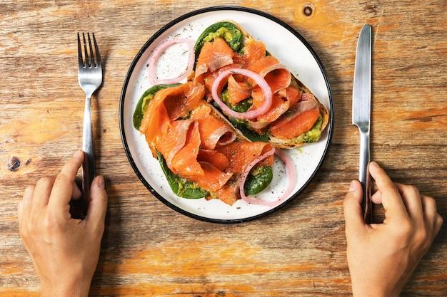 Женские руки и вкусные тосты с копченым лососем, авокадо и листьями  базилика | Премиум Фото