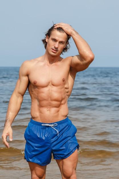 ビーチで筋肉の男 Premium写真