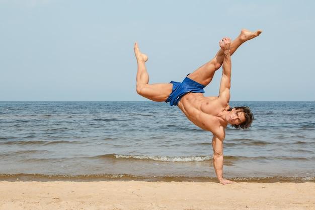 ビーチでトレーニングをしている男 Premium写真