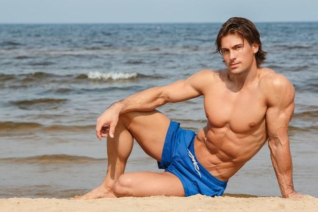Мускулистый мужчина на пляже Premium Фотографии