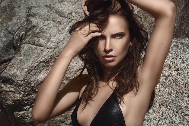 Красивая женщина на пляже с камнями Premium Фотографии