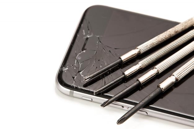 壊れたスマートフォンと小さなドライバーで修理 Premium写真