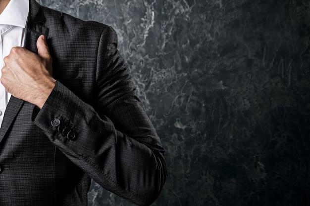 コンクリートの壁にスーツを着た男 Premium写真
