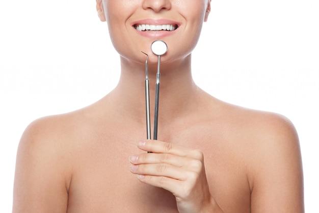 笑顔の女性と歯科用ツール Premium写真